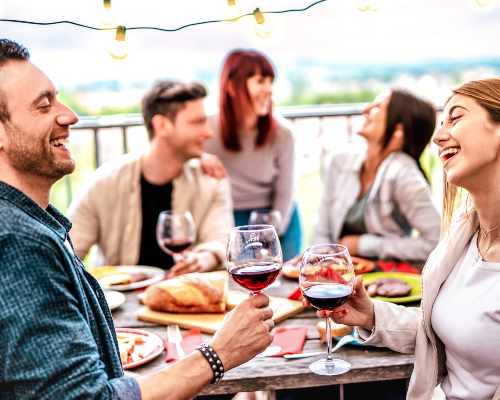 https://images.mirai.com/OFFERS%2FHOTELS%2F75522806%2Fhappy-people-having-fun-drinking-wine-on-terrace-at-private-dinner-party.jpg